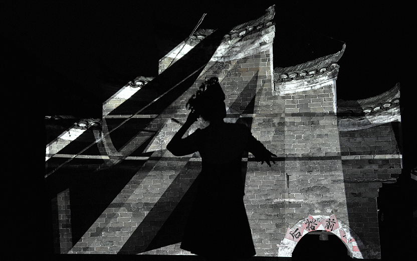 Woman's dancing being projected on the traditional architecture to create construction  projection - an interactive media design to demonstrate the cultural ecology of ethnic minorities in China   with an emphasis on participation and interaction